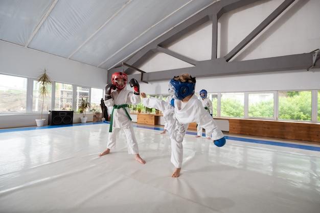 Attaquer avec la jambe. garçon portant un kimono blanc et un casque de protection attaquant son rival avec la jambe