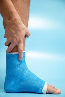 Attelle de cheville bleue. jambe bandée moulée sur un patient de sexe masculin sur fond flou bleu clair. concept de blessure sportive.