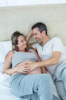 Attend un couple allongé sur le lit et discutant dans leur chambre