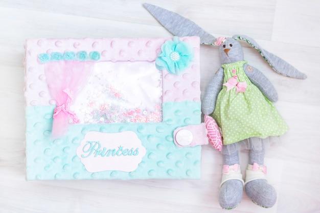 En attendant le bébé. fille. jouet lapin fille, boîte de princesse sur un fond en bois clair.