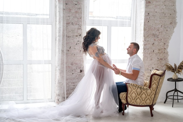 En attendant. heureuse paire enceinte en vêtements de mode qui pose en studio