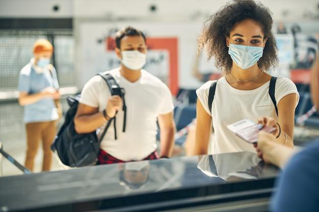 Attendez le portrait d'une femme heureuse donnant un passeport et un billet au personnel au comptoir d'enregistrement de l'aéroport
