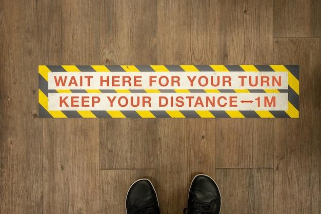 Attendez votre tour gardez votre signe de distance sur un étage de magasin