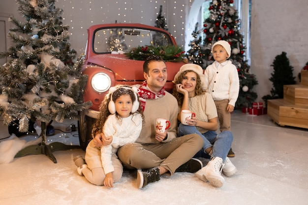 Attendre noel. joyeux parents et leur jolie fille et fils en attente de noël près de la voiture rouge