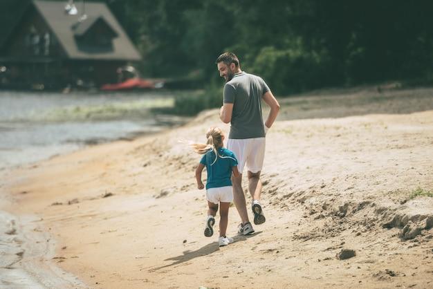 Attends-moi papa ! vue arrière sur toute la longueur du joyeux père et fille faisant du jogging ensemble au bord de la rivière
