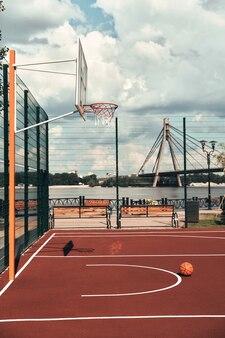 En attente de joueurs. coup de ballon de basket allongé sur le terrain de basket vide à l'extérieur