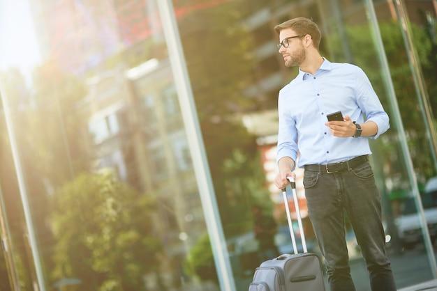 En attente de taxi élégant bel homme d'affaires avec une valise tenant un smartphone et en détournant les yeux