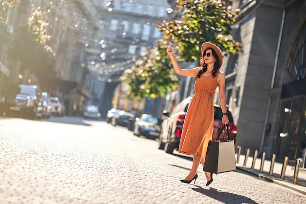 En attente de taxi. toute la longueur d'une jeune femme à la mode heureuse avec des sacs à provisions portant une longue robe d'été et des chaussures à talons hauts debout sur la route à l'extérieur. shopping, concept de mode de vie des gens
