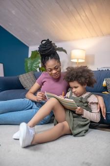 Attention, attention. jeune adulte mère souriante attentive à la peau foncée avec une petite fille peinture assise sur le sol dans une chambre moderne