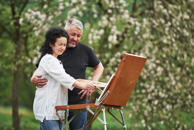 Attention aux détails. couple d'âge mûr ont des journées de loisirs et travaillent ensemble sur la peinture dans le parc