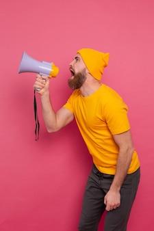 Attention! homme européen en colère criant dans un mégaphone sur fond rose