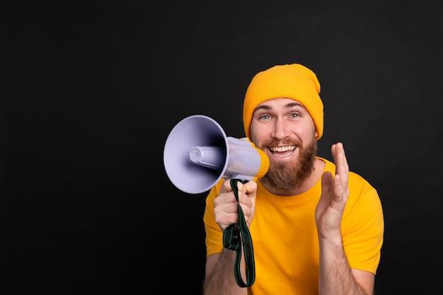 Attention! homme européen criant dans un mégaphone sur fond noir