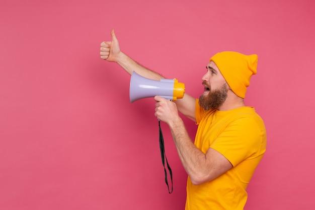 Attention! homme européen criant dans un mégaphone sur fond rose