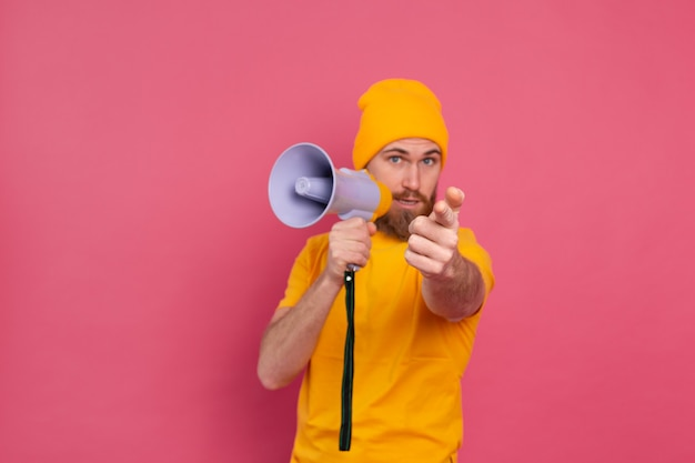 Attention! homme européen avec mégaphone doigt pointé vers la caméra sur fond rose