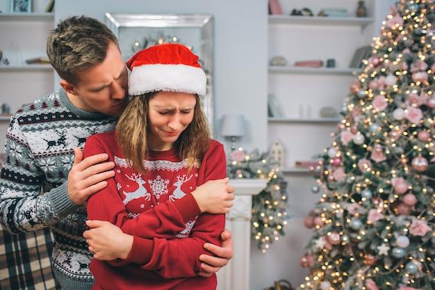 Attention jeune homme essayant de calmer la femme sourde. il se tient derrière elle dans une pièce décorée. elle s'embrasse et baisse les yeux. la femme pleure.