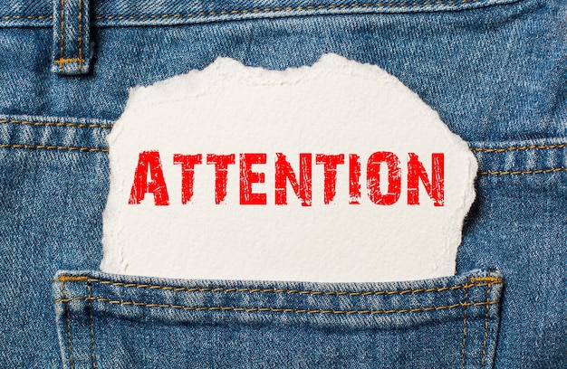 Attention sur papier blanc dans la poche de jeans en denim bleu