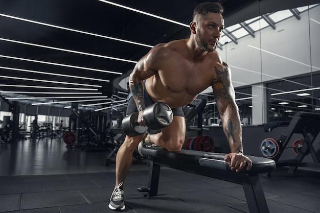 Attentionné. jeune athlète caucasien musclé pratiquant dans la salle de gym avec les poids. modèle masculin faisant des exercices de force, entraînant le haut du corps. bien-être, mode de vie sain, concept de musculation.