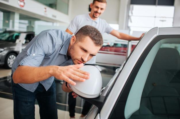 Attentive aux détails, la cliente s'appuie sur une voiture blanche et la touche. jeune homme regarde dans le miroir. il est sérieux et concentré. le vendeur se tient derrière lui et sourit. il est très positif.