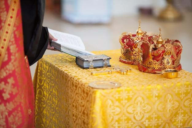 L'attirail de mariage de l'église orthodoxe - croix, bible et couronnes