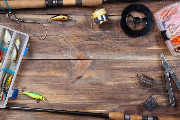 Attirail de pêche cadre et appâts de pêche dans des boîtes sur fond de planche de bois