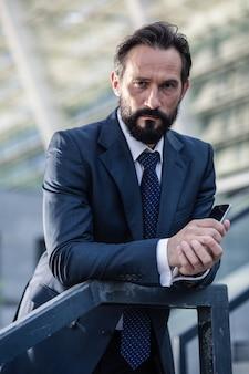 Attitude sérieuse. agréable homme d'affaires sérieux tenant un téléphone tout en vous regardant
