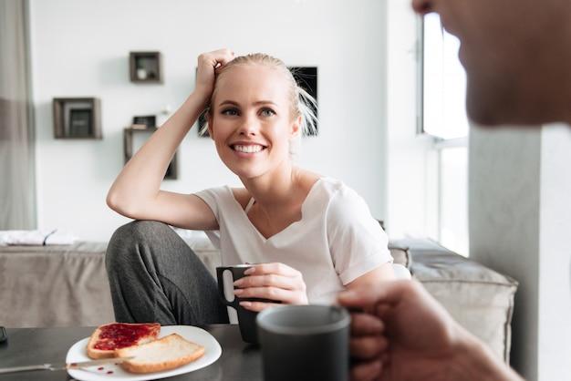 Attractive cheerful lady regardant son homme pendant qu'ils prennent le petit déjeuner