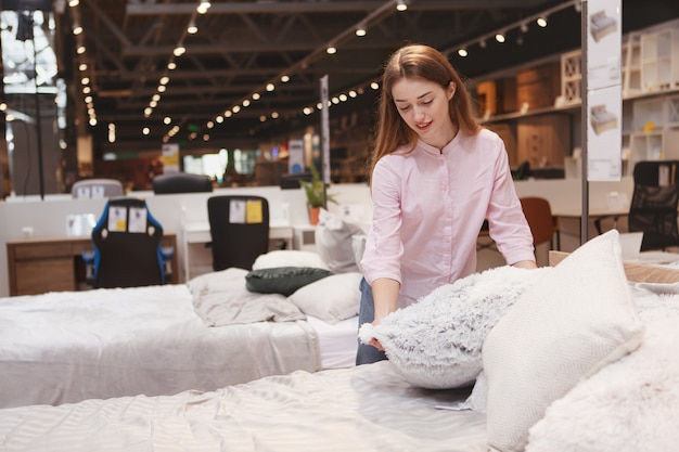 Attractive cliente examinant des coussins en vente au magasin de meubles local