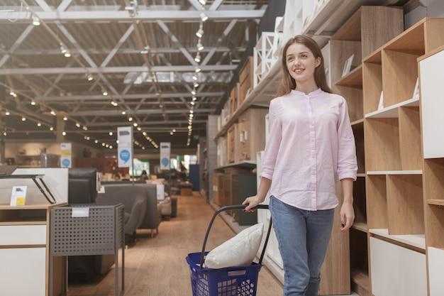 Attractive cliente marchant avec panier au magasin de meubles