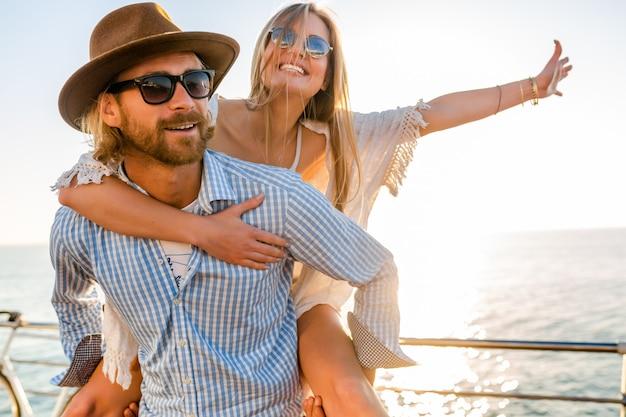Attractive couple heureux en riant voyageant en été par mer, homme et femme portant des lunettes de soleil