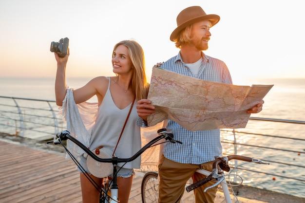 Attractive couple heureux voyageant en été sur des vélos, homme et femme aux cheveux blonds mode de style hipster boho s'amuser ensemble, à la recherche sur la carte des visites touristiques en prenant des photos à la caméra