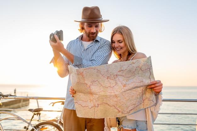 Attractive couple heureux voyageant en été sur des vélos, homme et femme aux cheveux blonds mode style hipster boho s'amuser ensemble