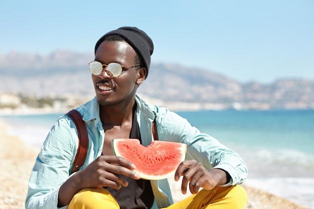 Attractive étudiant barbu passant du temps libre après l'université sur la plage urbaine