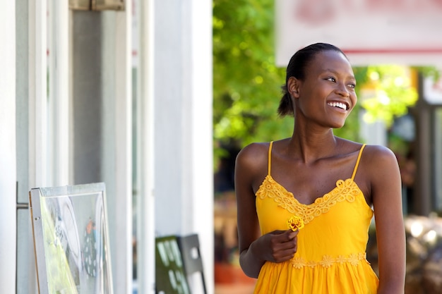 Attractive femme africaine marchant en plein air avec fleur