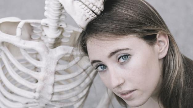 Attractive femme regardant la caméra à côté du squelette décoratif