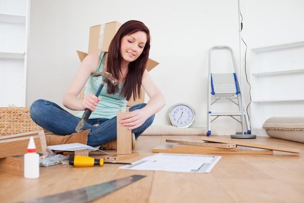 Attractive femme rousse clouer une planche à la maison