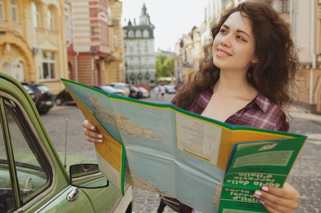 Attractive femme touriste utilisant une carte pour faire du tourisme