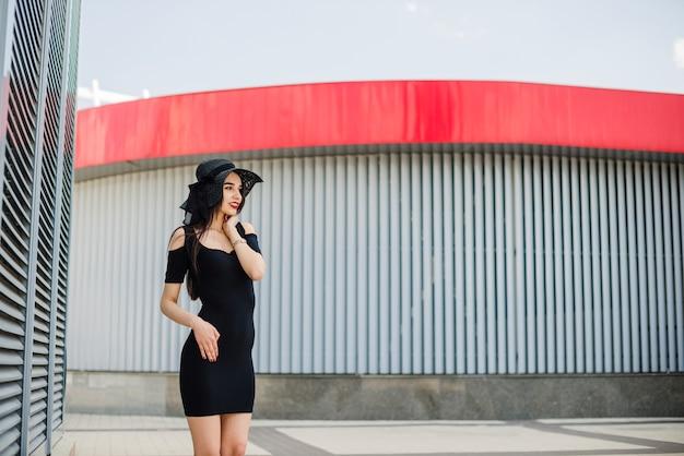 Attractive fille en tenue noire debout à l'extérieur