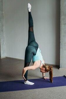 Attractive fit jeune femme sport porter fille fitness faisant des étirements à la classe d'entraînement studio loft