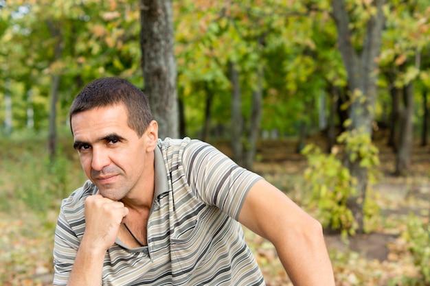 Attractive homme réfléchi moyen assis avec son menton sur son poing donnant à la caméra un léger sourire