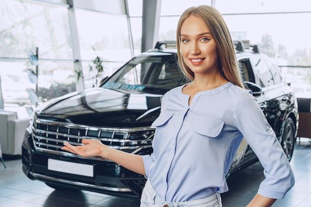 Attractive jeune concessionnaire automobile debout dans la salle d'exposition près d'une nouvelle voiture