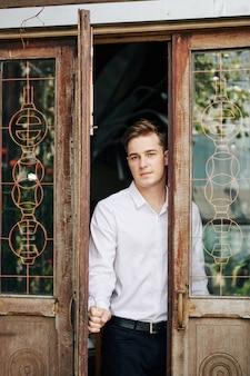 Attractive jeune homme sérieux ouvrant la porte en bois