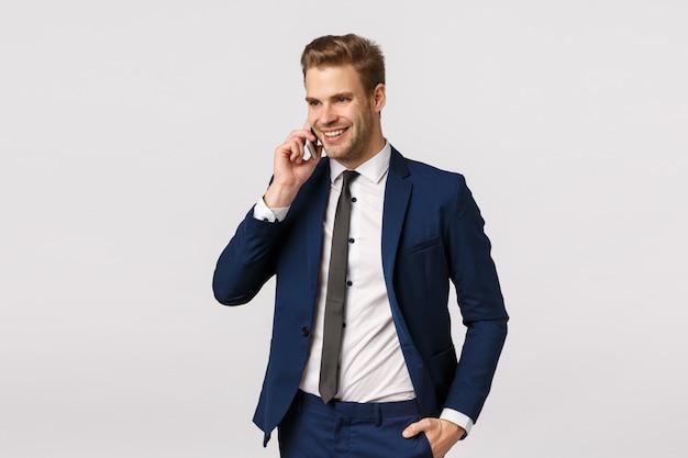 Attractive, prospère et riche jeune homme d'affaires caucasien en costume, parler au téléphone, tenant le smartphone près de l'oreille, appeler des partenaires commerciaux étrangers, discuter du personnel de l'entreprise, fond blanc