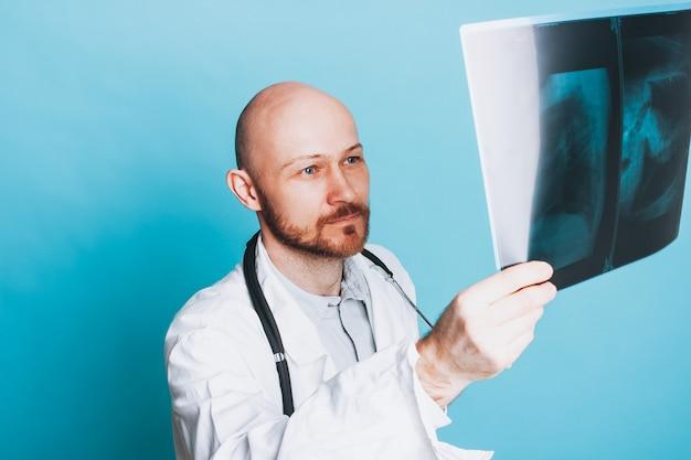 Attractive sympathique barbu chauve souriant médecin regardant radiographie isolé sur fond bleu