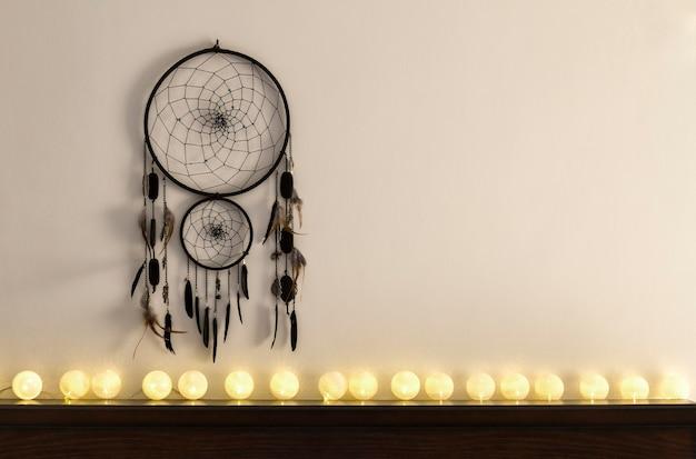 Attrape-rêves accroché au mur avec des guirlandes de boules de coton blanches
