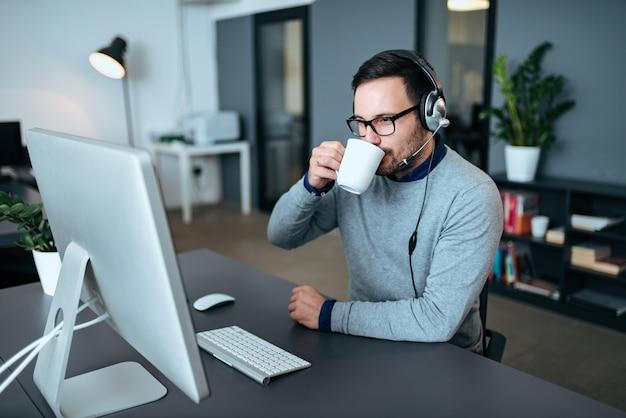 Un attrayant agent du centre d'assistance prend une pause-café après un appel.