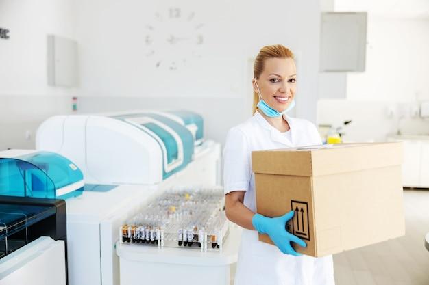 Attrayant assistant de laboratoire blond positif transportant une boîte avec des vaccins pour covid 19.