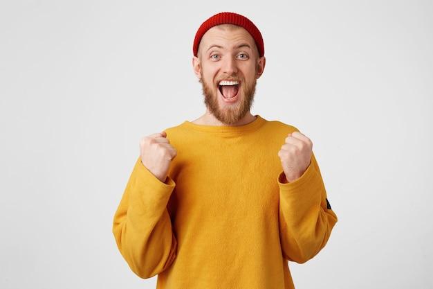 Attrayant cool beau barbu optimiste positif célébrant avec la bouche ouverte