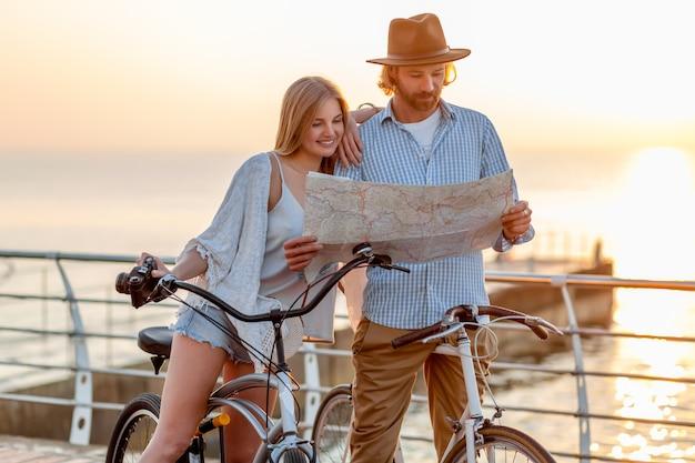 Attrayant couple heureux d'amis voyageant en été sur des vélos, homme et femme aux cheveux blonds mode style hipster boho s'amusant ensemble