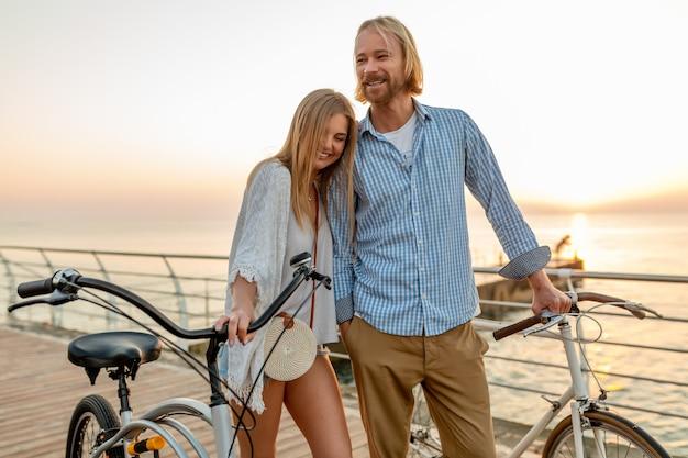 Attrayant couple heureux d'amis voyageant en été sur des vélos, homme et femme aux cheveux blonds mode de style hipster boho s'amuser ensemble, marcher au bord de la mer dans la ville de villégiature