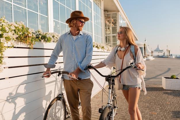 Attrayant couple heureux d'amis voyageant en été sur des vélos, homme et femme aux cheveux blonds